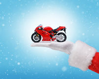La main dans le costume Santa Claus tient la motocyclette rouge Photos stock