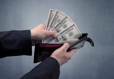 La main dans le costume sort le dollar du portefeuille Photos stock