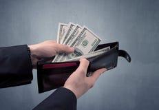 La main dans le costume sort le dollar du portefeuille Photographie stock libre de droits