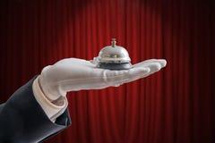La main dans le gant blanc tient la cloche de service Rideau rouge à l'arrière-plan photos stock