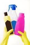 La main dans le gant jaune en caoutchouc tient la bouteille trois du détergent liquide sur le fond blanc Nettoyage Photographie stock libre de droits