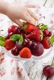La main de bébé prend une fraise mûre de plat Casse-croûte sain photographie stock