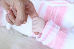 La main de bébé tenant le doigt de père, se ferment  Images stock