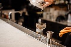La main de barman versant la boisson alcoolisée s'est mélangée à de la glace dans un verre Photographie stock