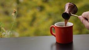 La main de barman versant le café chaud savoureux dans la tasse rouge a brassé dans le pot turc traditionnel, table de café dehor clips vidéos
