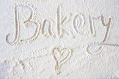 La main de boulangerie de mot écrite en farine sur une table en bois Images stock