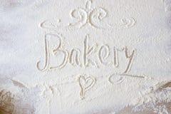 La main de boulangerie de mot écrite en farine sur une table en bois Coeur tiré par la main Photo libre de droits