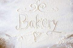 La main de boulangerie de mot écrite en farine sur une table en bois Coeur tiré par la main Photographie stock libre de droits