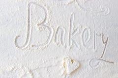 La main de boulangerie de mot écrite en farine sur une table en bois Gâteau en forme de coeur Images libres de droits