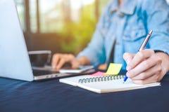 La main de femme écrit sur le bloc-notes avec un stylo et fonctionne dans un lapto Photos libres de droits