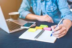 La main de femme écrit sur le bloc-notes avec un stylo et fonctionne dans un lapto Images stock