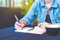 La main de femme écrit sur un bloc-notes avec un stylo dans le bureau Photographie stock libre de droits