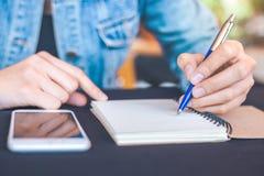 La main de femme écrit sur un bloc-notes avec un stylo dans le bureau Photo stock