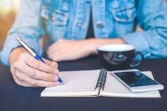 La main de femme écrit sur un bloc-notes avec un stylo dans le bureau Photographie stock
