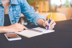 La main de femme écrit sur un bloc-notes avec un stylo dans le bureau Photos libres de droits