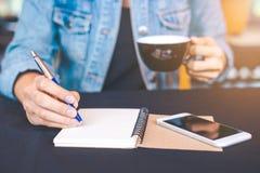 La main de femme écrit sur un bloc-notes avec un stylo dans le bureau Images stock