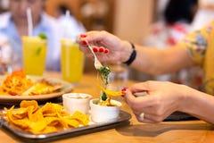 La main de la femme avec le clou de couleur rouge ayant une puce de tortilla avec de la sauce au fromage à nacho d'épinards avec  image libre de droits