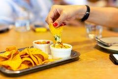 La main de la femme avec le clou de couleur rouge ayant une puce de tortilla avec de la sauce au fromage à nacho au temps de déje images libres de droits