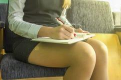 La main de femme d'affaires écrit sur le bloc-notes avec le stylo Photo stock