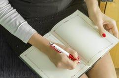 La main de femme d'affaires écrit sur le bloc-notes avec le stylo Images libres de droits