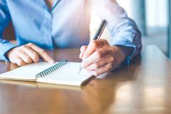 La main de femme d'affaires écrit sur le bloc-notes avec le stylo dans le bureau Image libre de droits