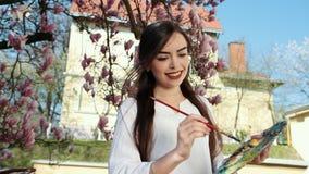 La main de la femme d'artiste avec l'image de peinture de brosse sur la toile dans la rue sur le fond de Sakura chic banque de vidéos