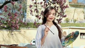 La main de la femme d'artiste avec l'image de peinture de brosse sur la toile dans la rue sur le fond de Sakura chic clips vidéos