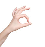 La main de femme dans l'ok se connectent un fond blanc Photographie stock libre de droits