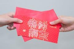 La main de femme donnant le rouge enveloppent contenir l'argent Photos stock
