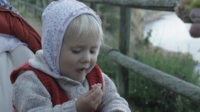 La main de la femme donne la nourriture à l'enfant Le bébé dans le hoodie et le gilet tricoté rouge mange le jambon se reposant d banque de vidéos