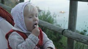 La main de la femme donne la nourriture à l'enfant Le bébé dans le hoodie et le gilet tricoté rouge mange le jambon se reposant d clips vidéos