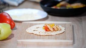 La main de femme fait le burrito mexicain traditionnel fait maison de nourriture banque de vidéos