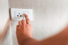 La main de femme met le commutateur en marche pour la lumière électrique dans une chambre à coucher, plan rapproché des doigts qu photo libre de droits