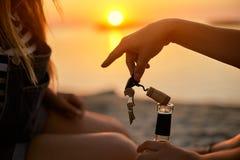 La main de femme ouvre avec élégance une bouteille de vin blanc avec le tire-bouchon et sort un bondon de liège Ouvreur de boutei images stock