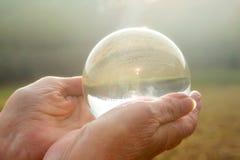 La main de femme plus âgée tenant une sphère en verre brillante photo libre de droits