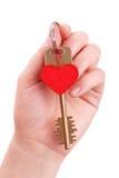 La main de femme retient une clé sur le coeur Photos stock