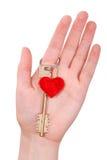 La main de femme retient une clé sur le coeur Photos libres de droits