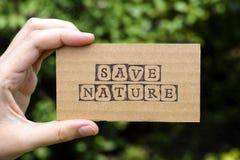 La main de femme tenant la carte de carton avec des mots sauvent la nature Image libre de droits