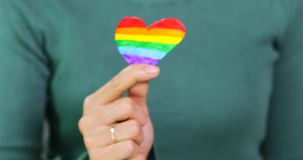 La main de femme tient la forme de coeur d'arc-en-ciel de drapeau de LGBT clips vidéos