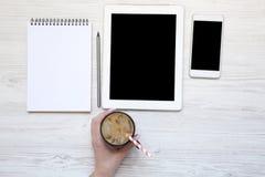 La main de femme tient une tasse de latte de glace Espace de travail féminin avec le sma Photo libre de droits