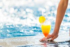 La main de la femme touchant un cocktail près d'une piscine Photo stock