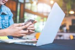 La main de femme utilisant un téléphone portable fonctionne dans le bureau images libres de droits