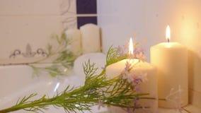 La main de femmes brûle des bougies dans la salle de bains De station thermale toujours durée banque de vidéos