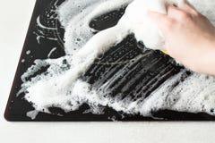 La main de femmes lave le fourneau électrique noir avec le détergent de savon Photographie stock