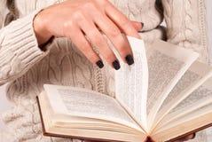 La main de femmes tient le morceau de papier de livre, elle est dans le chandail Photos stock