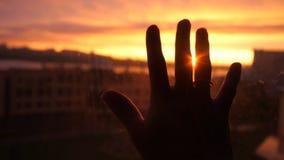 La main de femmes touche le soleil par la fenêtre sur le fond étonnant de ville de coucher du soleil Photographie stock