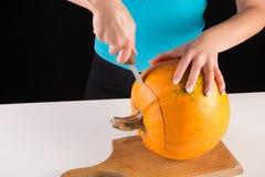 La main de fille coupe le grand potiron orange sur le conseil en bois photographie stock libre de droits