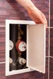 La main de fille ouvrent la boîte avec des mètres d'eau sur la salle de bains Photo stock