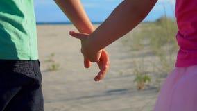 La main de la fille prend la main du garçon banque de vidéos