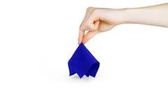 La main de fille soulève un tissu bleu sur un fond blanc Photos libres de droits